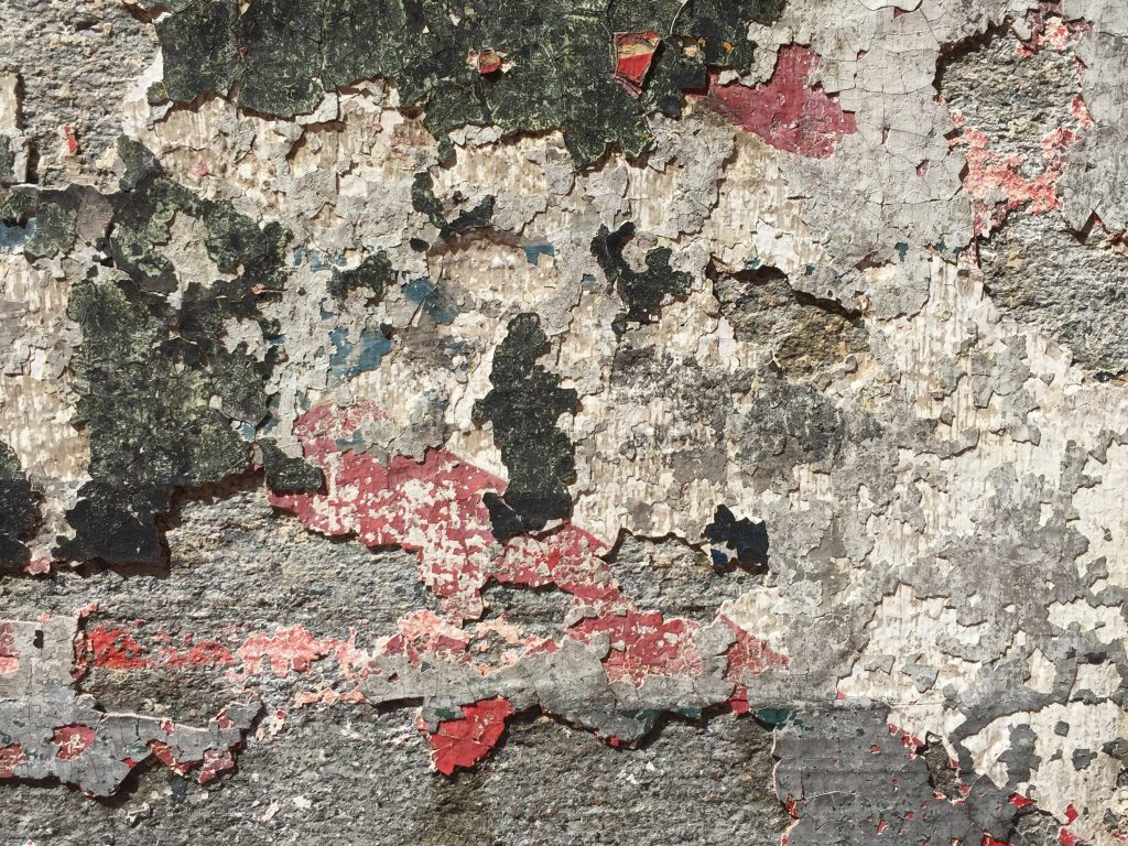 Old wall with chips of colorful plaster