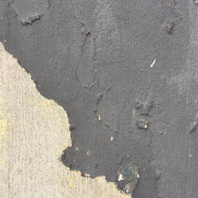 Dull black cracking paint on plaster over concrete