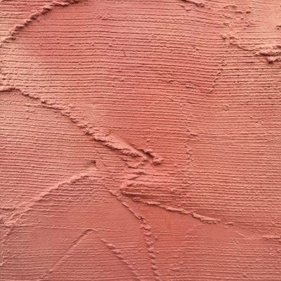 Pale red wall with horizontal lines in plaster