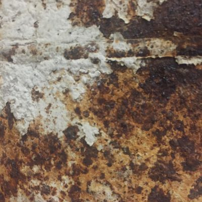 Grungy brown corrosion and rust with white paint