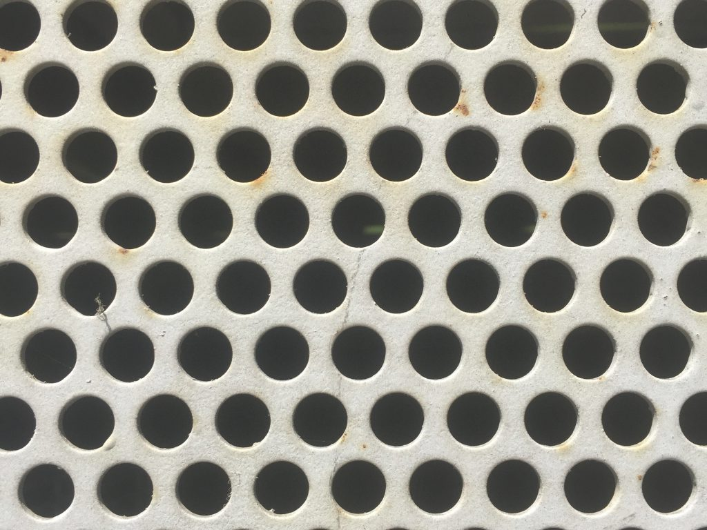 White metal with circles punched out