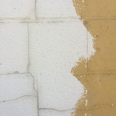 White and yellow paint over cracking cinderblocks