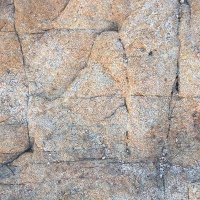 Rock surface with warm red color and breaks in surface