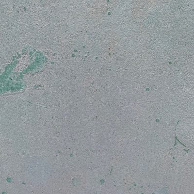 Concrete wall with coarse surface and sparse chips of teal paint
