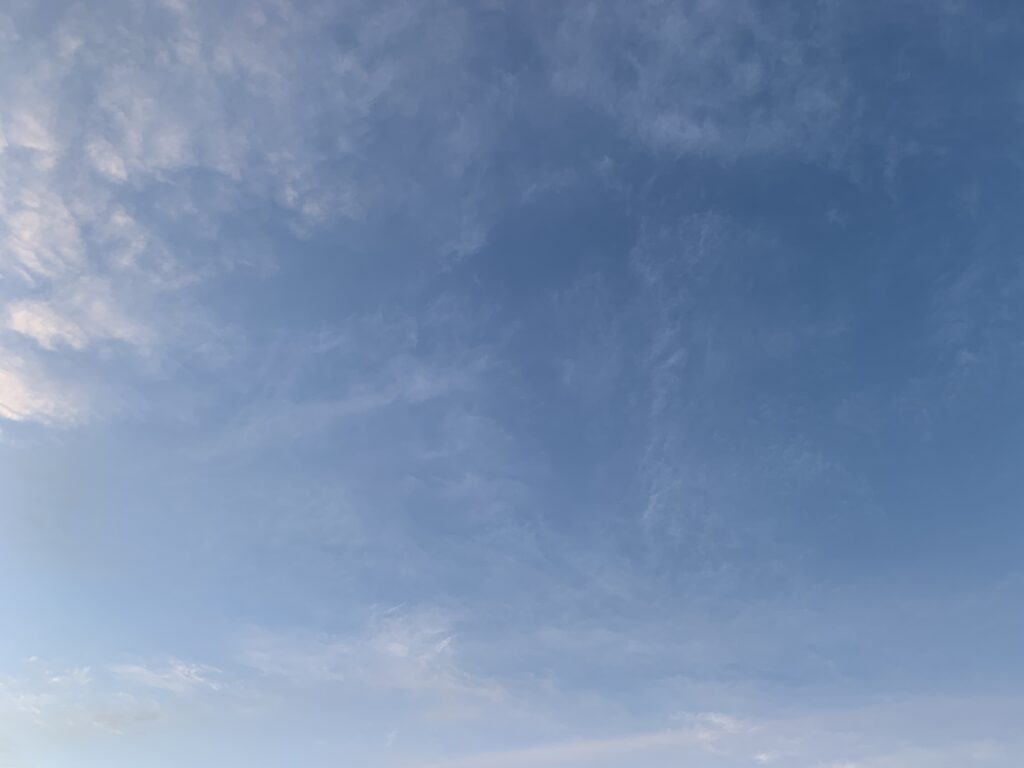 Light layer of clouds over gradient of blue sky