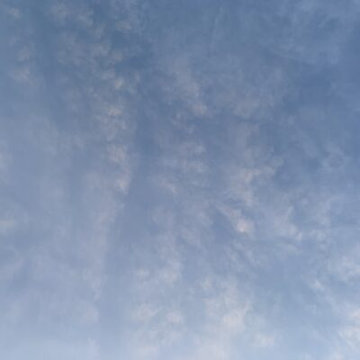 Fluffy white sparse clouds in gradient blue sky