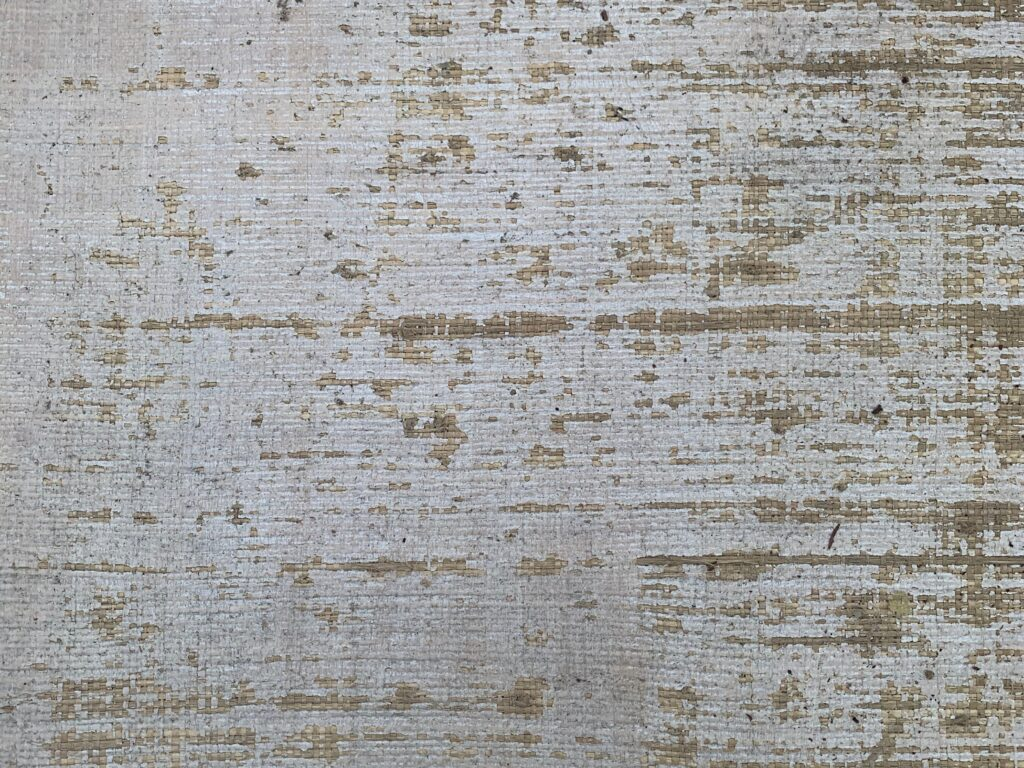 Crumbling off white paint on old wood