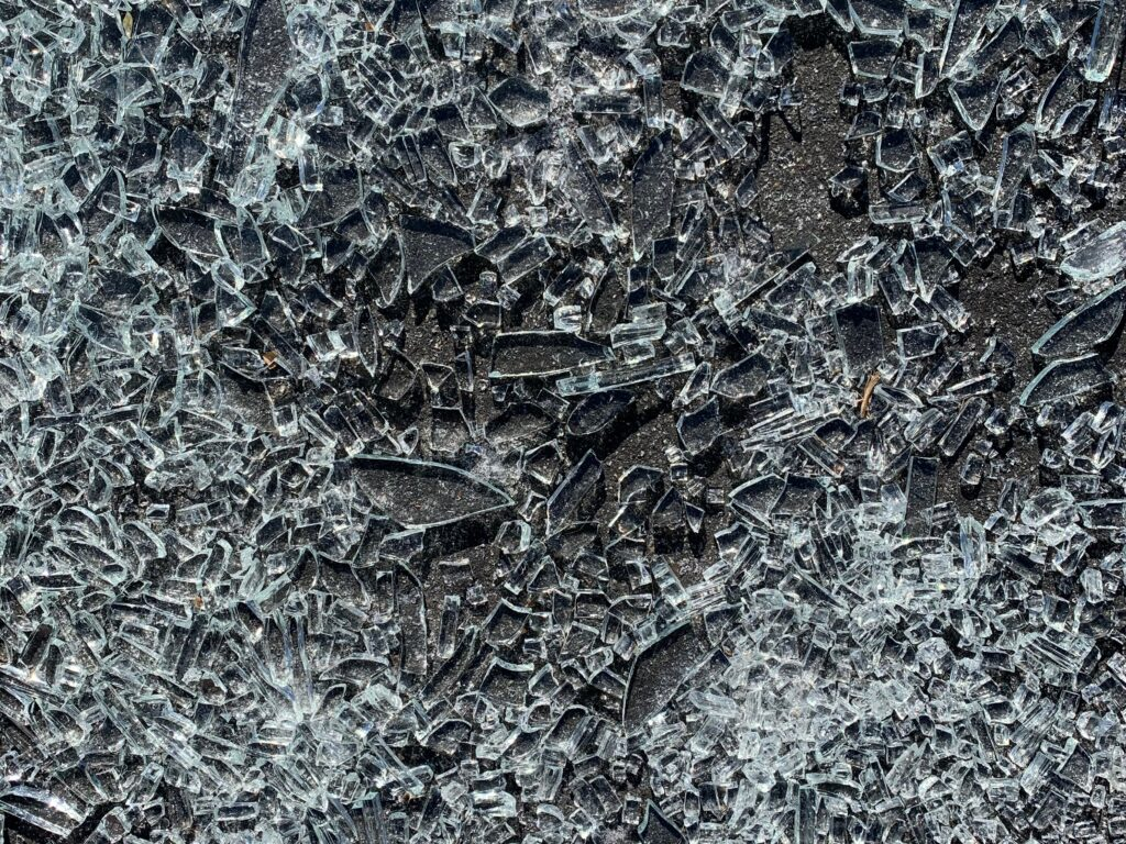 Charcoal gray concrete pavement covered in shattered glass