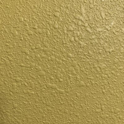 Pale yellow paint over textured stucco wall