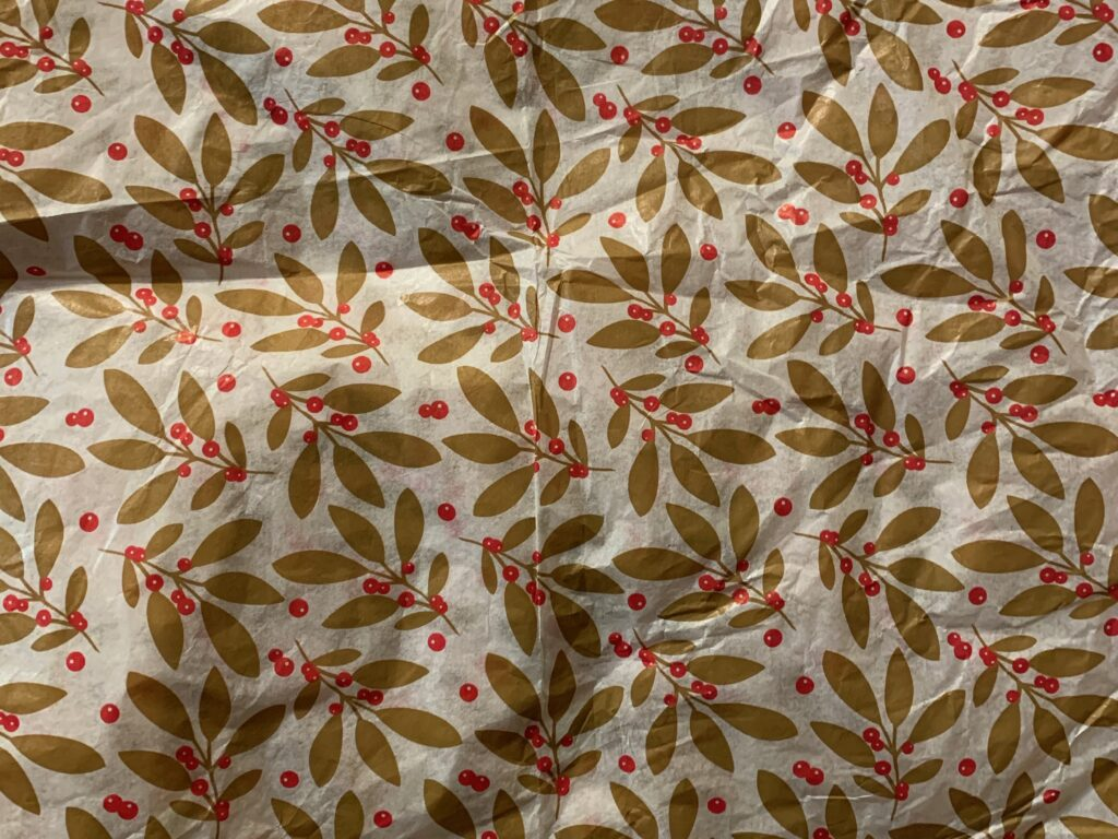 Decorative white gift wrap paper with golden floral pattern with red berries