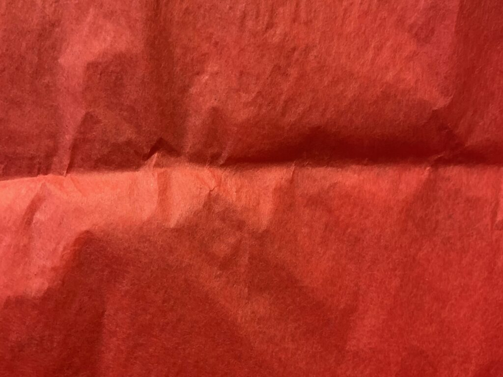 Vibrant red close up of delicate gift wrap paper