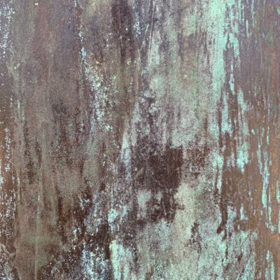Grungy and corroded metal surface with teal like color ove red rust