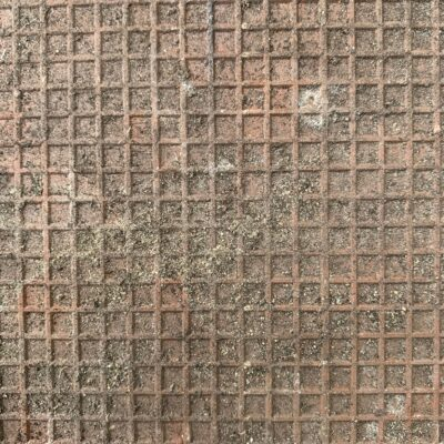 Rusty metal with square grid and dirt overlaying