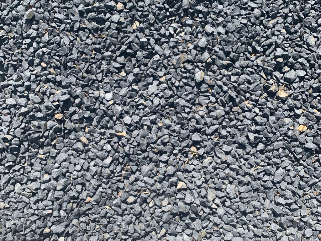 Small gray rocks with hard edges in flat patch of gravel