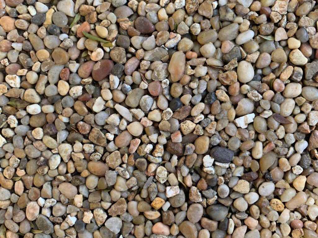 Uniform and colorful pebbles on flat surface
